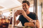 Happy young man eating a delicious burger at restaurant. Hungry young guy having stacked burger at fast food cafe.